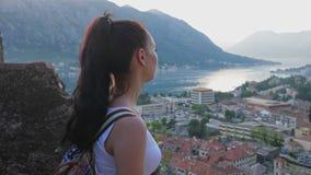 De toerist kijkt van een hoogte aan een baai in de bergen stock footage