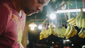 De toerist koopt vruchten in Aziatische bazaar stock videobeelden