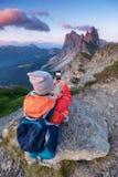 De toerist maakt een foto door een telefoon op de hoge bergbovenkant Avontuur en reisconcept stock foto's