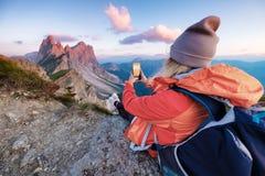 De toerist maakt een foto door een telefoon op de hoge bergbovenkant Mensen die in de bergen reizen DE ALPEN VAN HET DOLOMIET, IT stock afbeelding