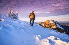 De toerist met rugzak die zich in de winteraard bevinden kromp door sneeuw ineen Mens die aan de bergen in laatste zonsondergangl Stock Fotografie