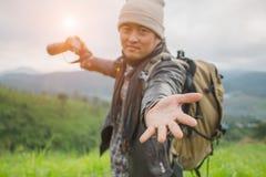 De toerist met rugzak op berghelling met opgeheven overhandigt, stock fotografie