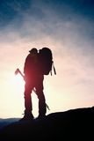 De toerist met sportieve rugzak en de polen in handen bevinden zich op klip en het letten op in diepe nevelige valleiblaasbalg De royalty-vrije stock foto