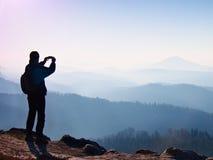De toerist neemt foto's met slimme telefoon op piek van rots Dromerig fogy landschap, de lente oranje roze nevelige zonsopgang in Royalty-vrije Stock Foto