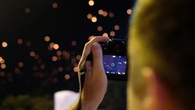 De toerist neemt video van vliegende vlammende lantaarns bij vakantie krathong in Chiang Mai Thailand stock video