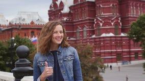 De toerist op reis glimlacht omhoog en heft zijn duim op stock videobeelden