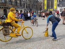 De toerist plaatst schenking in de uitvoerders gele mens op gele fiets c royalty-vrije stock foto's