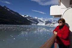 De toerist in rood jasje op cruiseschip bewondert landschap Stock Afbeeldingen