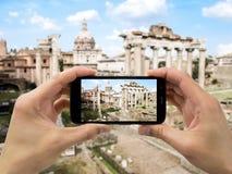 De toerist steunt camera mobiel bij forum in Rome stock afbeelding