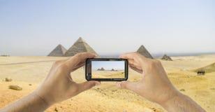 De toerist steunt camera mobiel bij piramides stock afbeeldingen
