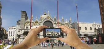 De toerist steunt cameratelefoon bij de Basiliek van San Marco in v royalty-vrije stock foto's