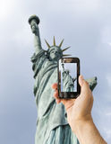 De toerist steunt cameratelefoon bij standbeeld van vrijheid stock foto