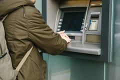 De toerist trekt geld van ATM voor verdere reis terug Draait de code met één hand en sluit de knopen met royalty-vrije stock afbeeldingen
