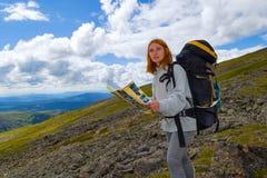 De toerist van het roodharigemeisje maakt een route op de kaart in haar handen, stock foto's