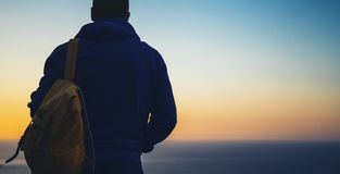 De toerist van de Hipsterwandelaar met rugzak het kijken van verbazende zeegezichtzonsondergang op blauwe overzees als achtergron royalty-vrije stock afbeeldingen