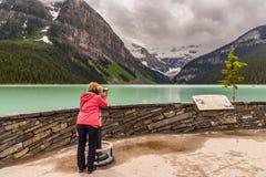 De toerist van meerlouise het bekijken bergen en bewolkte hemel Canada stock afbeelding