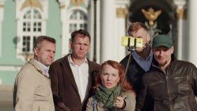 De toerist vraagt gids over monument, gidsantwoorden Andere toeristen maken foto en selfie stock footage