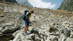 De toerist zet op een wandelingsrugzak en gaat op een berg beklimmend route stock video