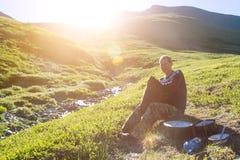 De toerist zit met een rugzak bij zonsopgang royalty-vrije stock afbeeldingen
