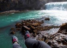 De toerist zit op een klip dichtbij de rivier, die zijn benen hangen neer, v stock afbeeldingen