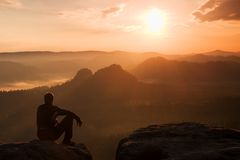 De toerist in zwart windjasje zit op scherp rots en horloge in kleurrijke nevelige valleiblaasbalg Zonnige de lentedageraad in ro Royalty-vrije Stock Foto