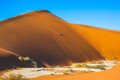 De toeristen beklimmen de scherpe rand van hoge duinen Stock Afbeelding
