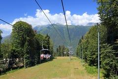 De toeristen berijden de kabelwagen in de bergen van de Kaukasus dichtbij r stock foto's