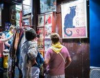 De toeristen bestuderen herinneringen buiten winkel onder avondlichten op Montmartre, Parijs Royalty-vrije Stock Fotografie