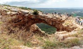De toeristen bevinden zich en bekijken het Keshet-Hol - oude natuurlijke kalksteenboog die de overblijfselen van een ondiep hol m royalty-vrije stock foto
