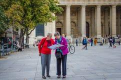 De toeristen controleren hun kaart op Plaats St Sulpice Stock Fotografie