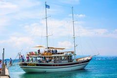 De toeristen dalen van het schip onder Griekse vlag in haven van Ouranoupoli-dorp, Griekenland Stock Afbeeldingen