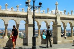 De toeristen die het Parlement mening door Fishermans-Bastion kijken en nemen beelden op Buda Hill dichtbij oude steenomheining royalty-vrije stock foto