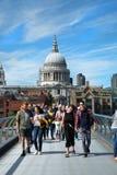 De toeristen die op millennium lopen overbruggen in Londen Stock Afbeelding
