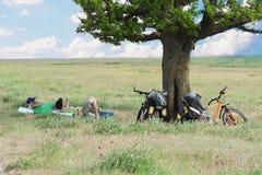 De toeristen die van de fiets dichtbij boom rusten Royalty-vrije Stock Fotografie