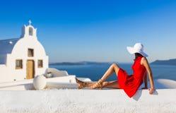 De toeristen donkerbruine vrouw die van de Santorinireis in rode kleding beroemd wit Oia dorp bezoeken stock afbeeldingen