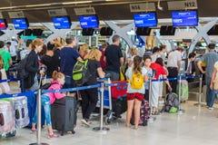 De toeristen en de reizigers wachten in lijn om hun luggages te controleren stock foto's