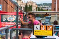 De toeristen genieten van bezienswaardigheden bezoekend hop-op-hop-weg reis op een stadsbus binnen stock afbeelding