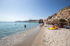 De toeristen genieten van het duidelijke water van het mooie Firiplaka-strand Stock Foto
