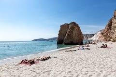 De toeristen genieten van het duidelijke water van het mooie Firiplaka-strand Stock Foto's