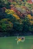 De toeristen genieten van de reis van de bootcruise en mooi omringend de herfstgebladerte Stock Foto