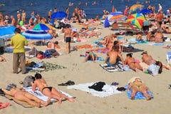 De toeristen hebben een rust op het zandige strand Stock Foto