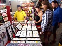 De toeristen kiezen van een verscheidenheid van herinneringsproducten bij een opslag of winkelen in Chinatown, Singapore Royalty-vrije Stock Fotografie