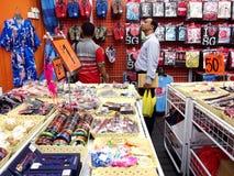De toeristen kiezen van een verscheidenheid van herinneringsproducten bij een opslag of winkelen in Chinatown, Singapore Stock Afbeelding