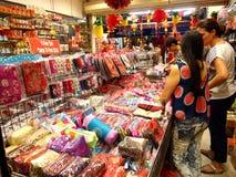 De toeristen kiezen van een verscheidenheid van herinneringsproducten bij een opslag of winkelen in Chinatown, Singapore Stock Fotografie