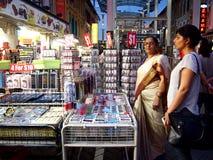 De toeristen kiezen van een verscheidenheid van herinneringsproducten bij een opslag of winkelen in Chinatown, Singapore Stock Afbeeldingen
