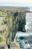 De toeristen kijken moedig onderaan een klip stock foto
