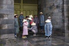 De toeristen kleedden zich in plastic regenjassen en kegelhoeden die samen in steenportiek huddling, Hue Imperial City stock foto's