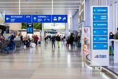 De toeristen komen bij de internationale Luchthaven van Praag klaar om de luchthaven te verlaten en hun vakantie te beginnen aan stock afbeeldingen
