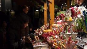 De toeristen kopen snoepjes bij een suikergoedkiosk bij de Kerstmismarkt stock video