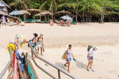 De toeristen lopen aan een passagiersboot op een wit strand in Thiland stock foto